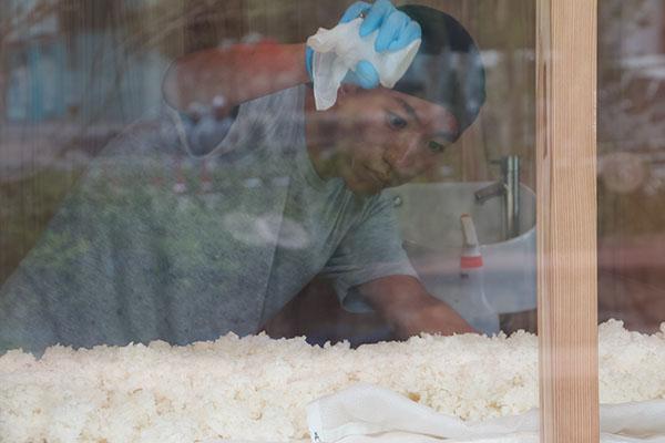 真剣な眼差しで麹の種付け(蒸し米に麹菌を振りかける工程)をする